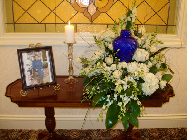 Blue urn surrounded by flowers on a table across from a photo in a frame