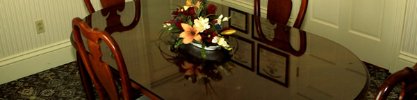 Photo of a table and chairs with a flower arrangement on it