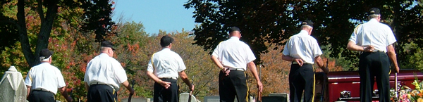 Veterans standing with their backs to the camera next to a casket at a cemetery
