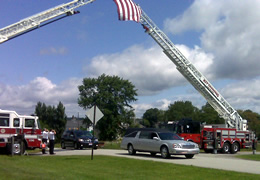 two firetrucks one opposite sides with their ladders extended to form an arch and a hearse driving under them